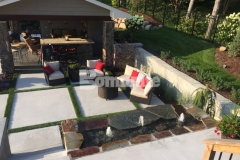 Bomanite Revealed was installed in this backyard resort to create the steps, landing, and courtyard area, using planting pockets and inlays of grass to help with drainage, break up the expanse of concrete, and add warmth to the space.